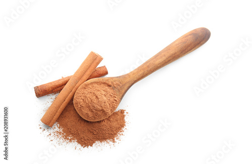 Spoon with cinnamon powder and sticks on white background Fototapeta