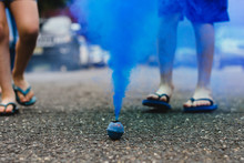 Blue Smoke Bomb In Street With Children's Feet