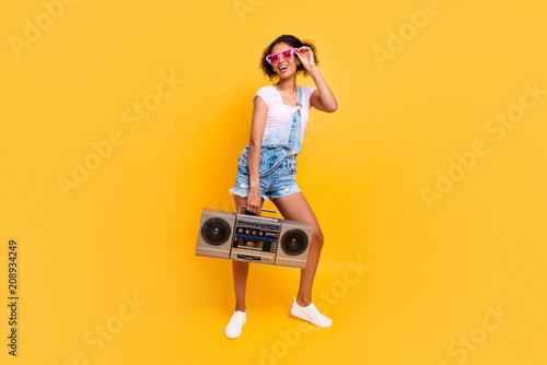 Fotografia  Full size portrait of cheerful positive girl in eyewear jeans overall holding boom box in hand going to make party isolated on yellow background