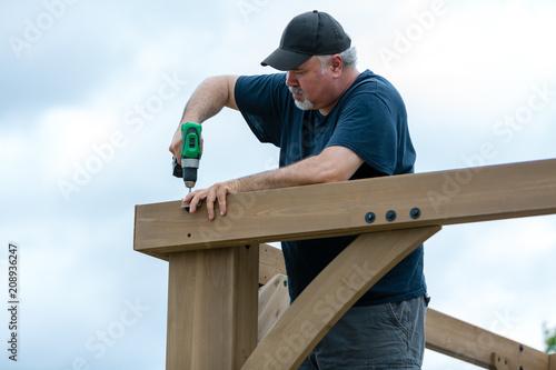 Fotografie, Obraz  Mature man building wooden construction