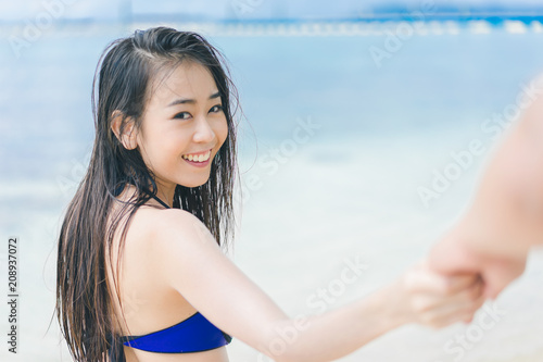 Keuken foto achterwand Ontspanning Pretty beautiful asian woman wearing blue swimwear bikini holding hand with her boyfriend