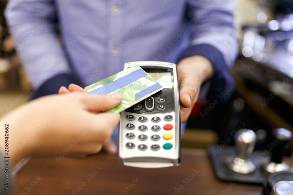 Fototapeta Photo of buyer man with bank card and seller with terminal in hand
