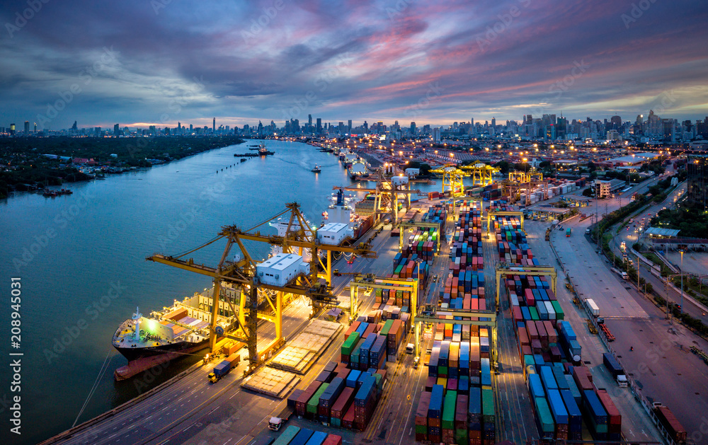 Fototapety, obrazy: Aerial view of international port with Crane loading containers in import export business logistics with cityscape of Bangkok city Thailand at night