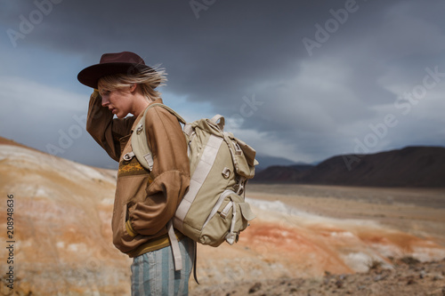 Valokuva  Portrait иeautiful young girl in hare, hat and with backpack travels among sands