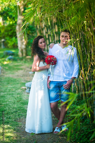 Photo The bride and groom stand near bamboo trees in the tropics