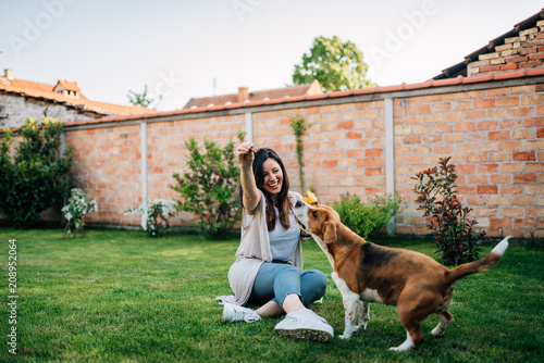 Fun time. Girl playing with her dog in the backyard. Wallpaper Mural