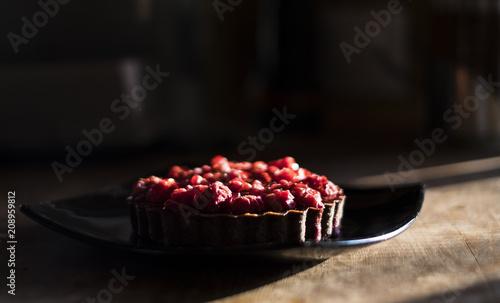 Papiers peints Buffet, Bar Raspberry tart on wooden table in the sunlight