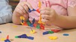 Close-up of unknown child playing with building kit indoor in kindergarten
