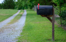 Rural Mailbox With Flag Raised Along A Gravel Road.