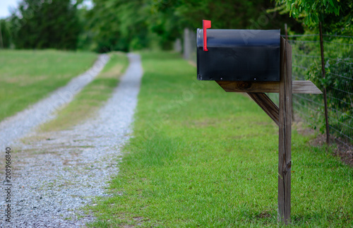 Fotomural Rural mailbox with flag raised along a gravel road.