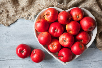 Red apples in a basket shaped like heart on a table