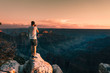 young man stays on the edge of the rock and takes a picture of Magnificent Grand Canyon, Arizona, USA.