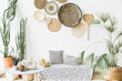 Leinwanddruck Bild - Modern minimal home interior design. Pillows, golden teapot, decorative straw plates, Scandinavian blanket, tropical palm tree, succulent and decorations.