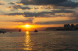 Cargo ship leaving the harbor, sailing out to sea with a beautiful sunset