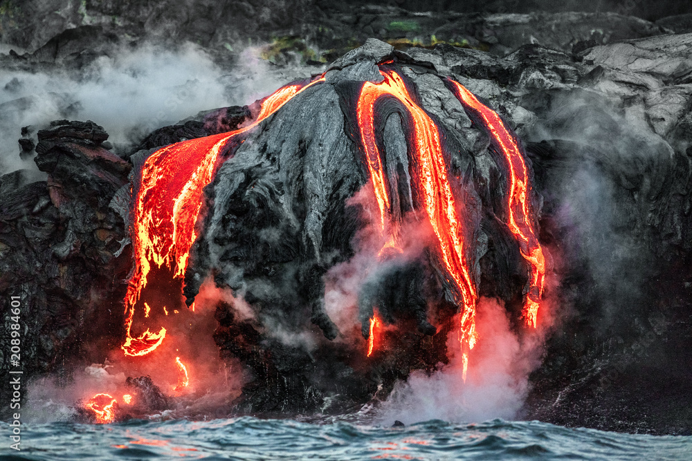 Fototapeta Hawaii lava flow entering the ocean on Big Island from Kilauea volcano. Volcanic eruption fissure view from water. Red molten lava.