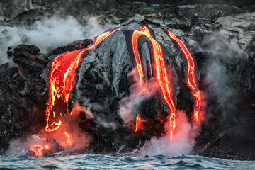 Hawaii lava flow entering the ocean on Big Island from Kilauea volcano. Volcanic eruption fissure view from water. Red molten lava.