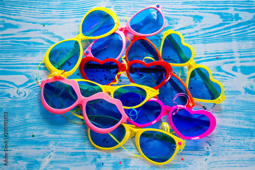b9178f4c1db Collection of colorful sunglasses on blue wooden background. Kid s party  concept. Funny fashion glasses