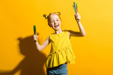 Girl With Red Hair On A Yellow Background. A Beautiful Girl Is Holding Colored Pencils In Her Hands.