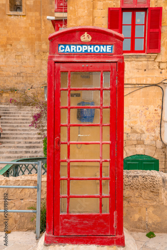 Poster London Valletta, Malta - Red vintage british telephone box and footbridge and traditional red balconies in the ancient city of Valletta early in the morning