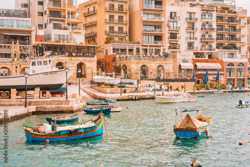 Fototapeta May 20, 2018. St. Julian. Malta. Beautiful old town of St. Julian on the island of Malta with colourful boats, bay, promenade and a statue of a fisherman with a cat and a fish. obraz