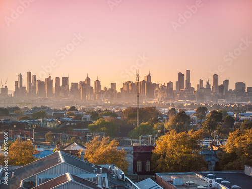 Skyscrapers in Melbourne's CBD in morning mist. Elevated view overlooking residential houses in western suburbs and modern buildings in city. Footscray, VIC Australia.