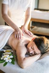 Obraz na płótnie Canvas Female message therapist giving a massage at a spa