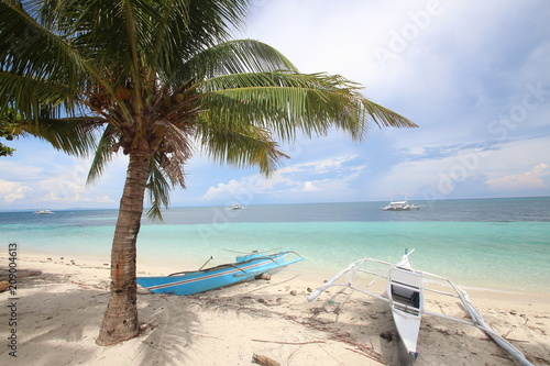 Colorful wooden boats on a beautiful tropical island white sandy beach