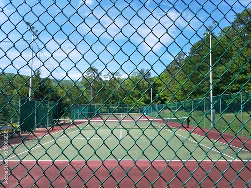 metal fence and green and red tennis court