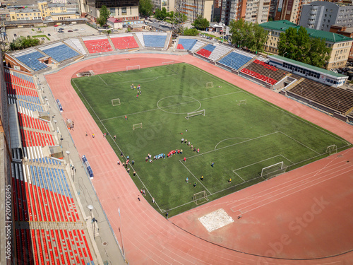 Fotografía  Aerial photography of a modern  stadium with green field for football, a big road, city traffic and parks on a warm summer day