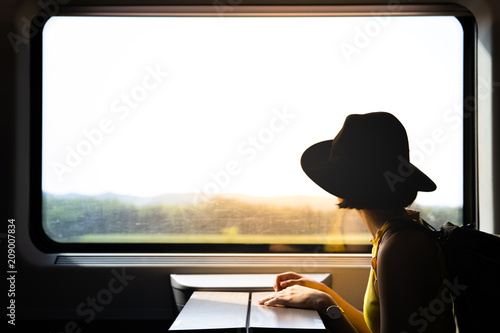 A beautiful hipster asian woman traveling on the train looking to the view through the window.