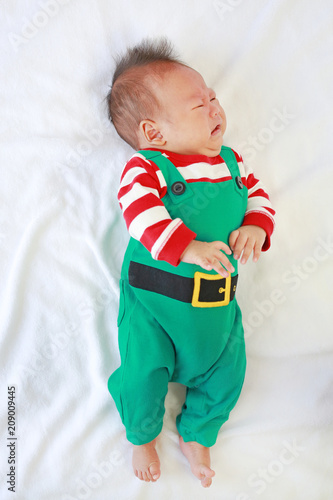 ad9d0fa3a Newborn baby boy in christmas bodysuit crying and lying on white fur ...