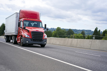 Bright red big rig semi truck with cab spoiler transporting semi trailer with commercial cargo