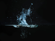 Droplet Of Water Dropped Into Liquid And Photographed While Making Splash On Surface. Water Splash Isolated On Dark Background. Explosion On The Water Surface, Abstract Backgrond. Plash Of Liquid