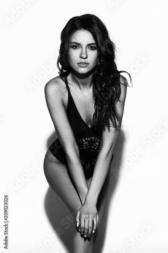 aa855b2d42 Young sexy slim tanned woman in black swimsuit posing against white  background. Black and white fashion portrait of beautiful girl with long  wavy brunette ...