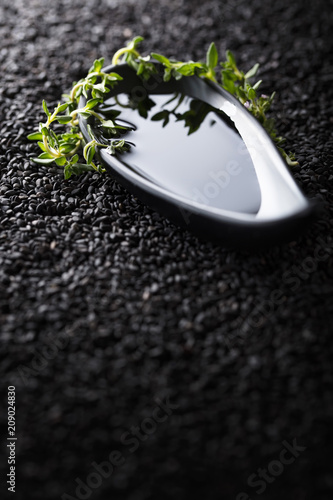 In de dag Aromatische Plant oil with thyme branches on a background of black sesame.