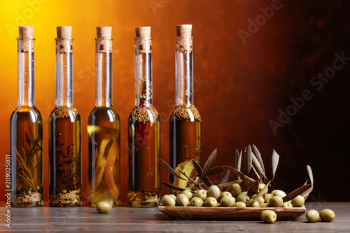In de dag Aromatische Green olives and bottles of olive oil with warious spices and herbs .