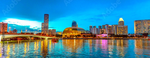 Acrylic Prints Singapore Skyline of Singapore in marina bay with cruise sails in the harbor at blue hour. Tourist boat on foreground. Night scene waterfront in Singapore bay.