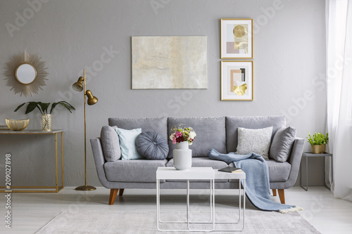 Fotobehang Sportwinkel Grey sofa with pillows and blanket standing in bright living room interior with gold lamp, fresh flowers on white table and carpet on the floor