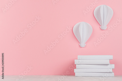 Poster Montgolfière / Dirigeable Pile white books and decorative hot air balloons of papers on white desk and soft pink background. Back to school background with copy space.