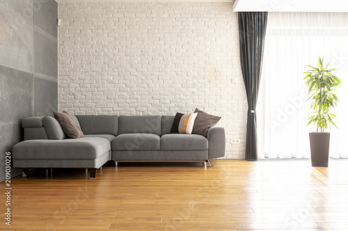 Fotobehang Sportwinkel Grey corner couch on wooden floor against brick wall in bright apartment interior with plant. Real photo