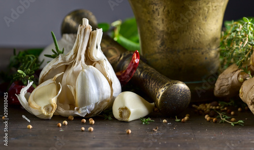 In de dag Aromatische Garlic and different spices on a wooden table.