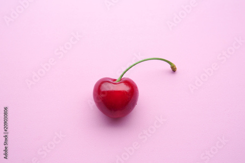 closeup of one cherry on pink background