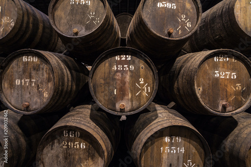 Fotografering Row of wooden porto wine barrels in wine cellar Porto, Portugal.