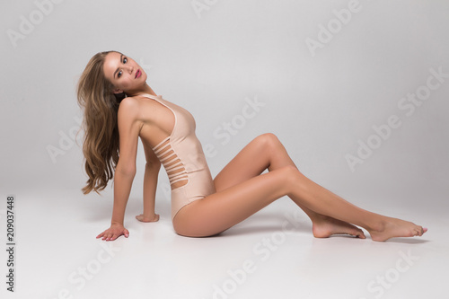 Tuinposter Akt Be in manner! Charming smiling beautiful lady in lingerie sitting on the floor on isolated background and posing for the picture.