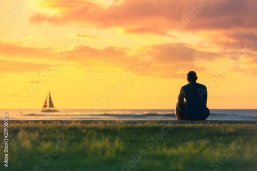 Cuadros en Lienzo Man relaxing by the sea watching the colourful sunset and sail boats go by