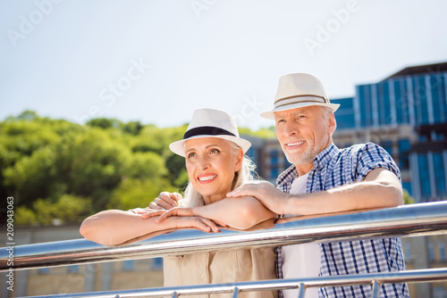 Fotobehang Sportwinkel Portrait of attractive cheerful couple in straw hats casual outfit enjoying beautiful view lean on balcony railing looking away spending time together. Vacation weekend holiday concept