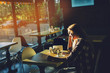 Young female student sitting in modern coffe shop. Sunset.Woman sitting in front of the window in cafe.