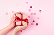 canvas print picture Woman's hands holding kraft gift box with red bow on pink background decorated with confetti.. Top view, holiday present concept.