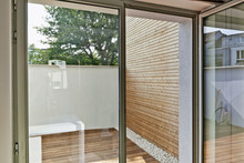Renovated White Ciment Wall And Insulating Wood Cladding In Outdoor Courtyard Truth Open Door Windows