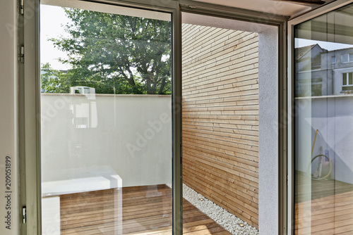 Fotografija Renovated white ciment wall and insulating wood cladding in outdoor courtyard tr